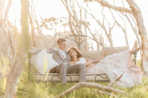 bride and groom sitting in couch amongst trees