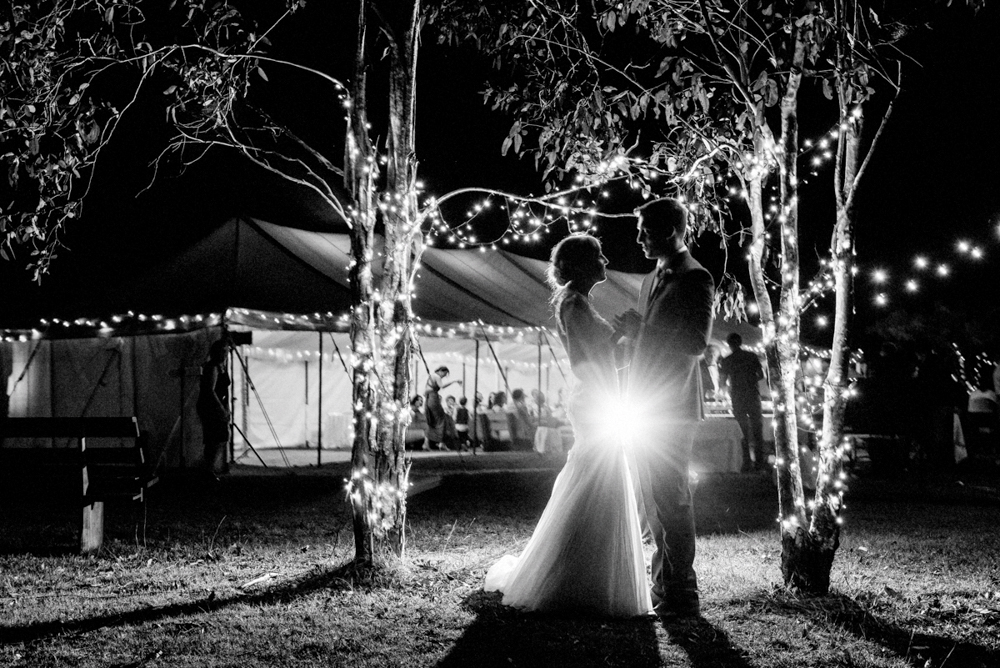 bride and groom kiss in front of marquee