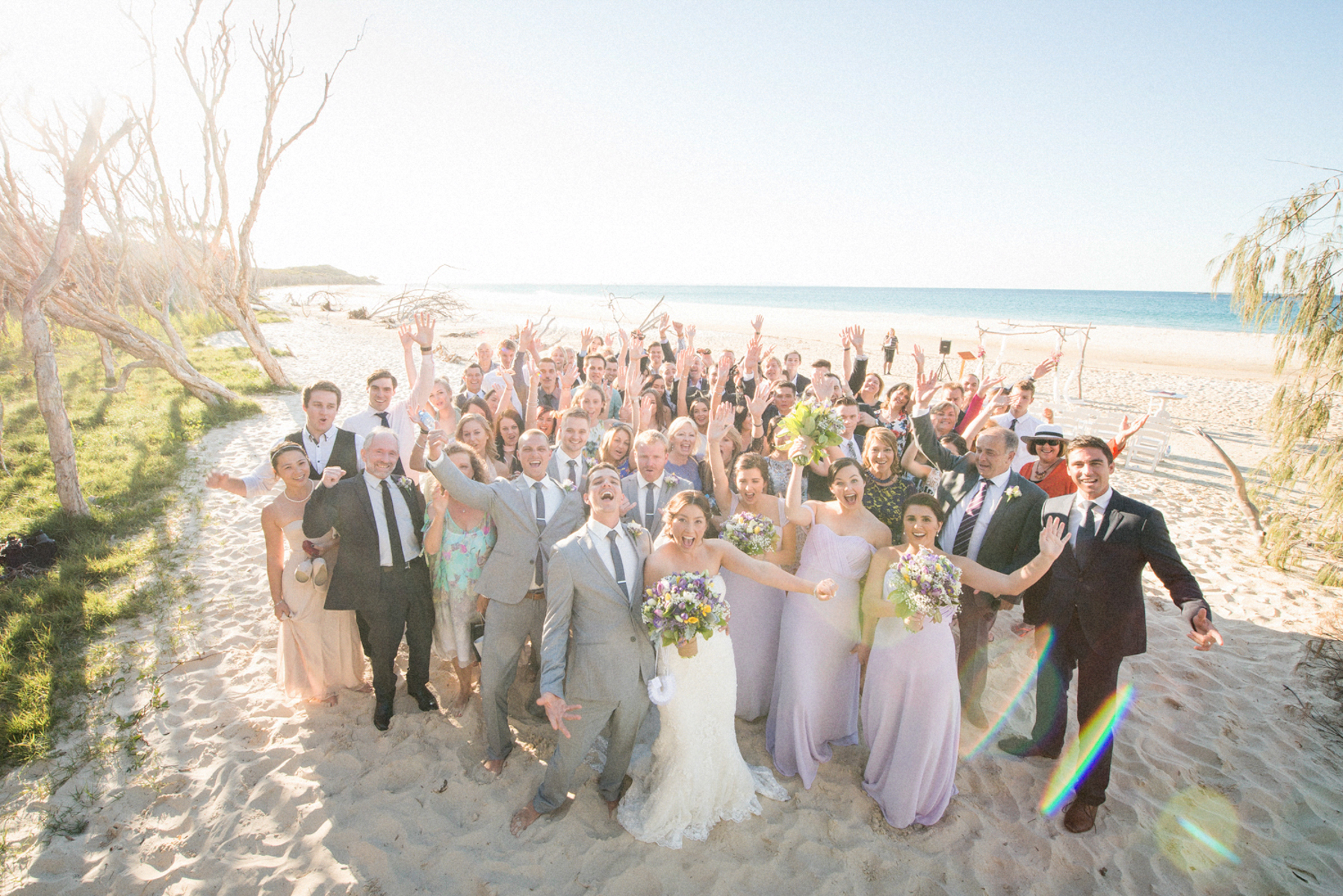 group photo of wedding guests on the beach