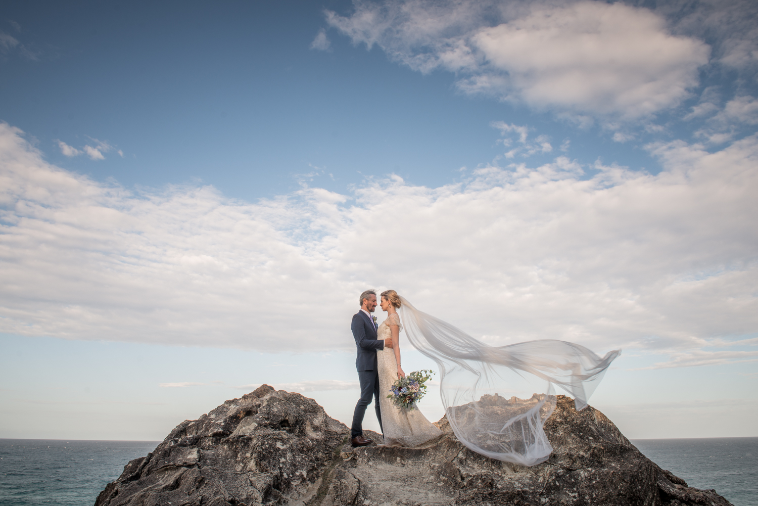 bride and groom in the wind on the rocks