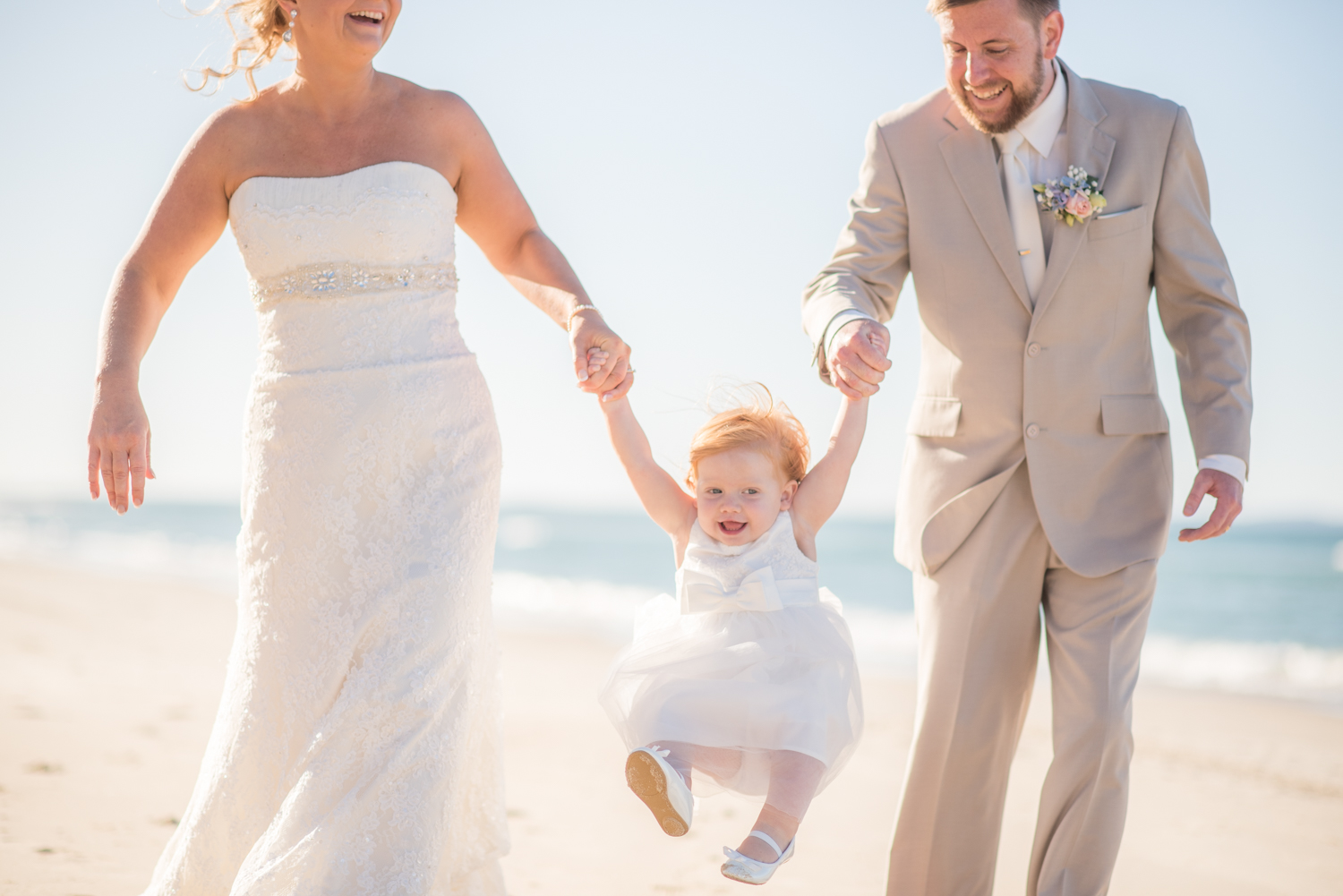 newlyweds with their baby girl on the beach