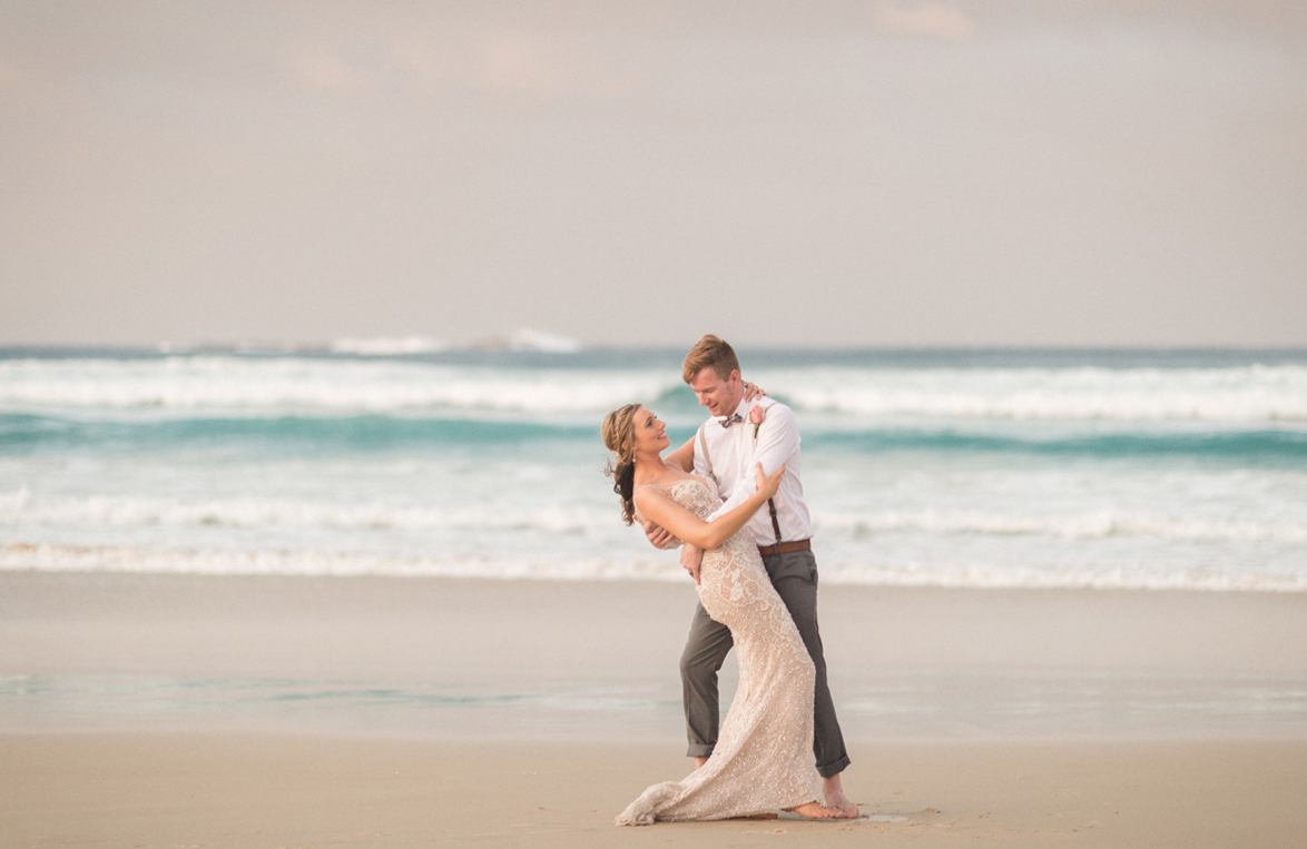 newlyweds on home beach at sunset